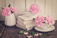 Pink carnation flowers in white tea cup stock image