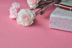 Pink carnations and floral notebook with a pen on a bright pink background, styled feminine image with copy space Stock Photography