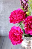 Pink carnations flower bouquet in metal  vase on rustic wooden background Royalty Free Stock Photo