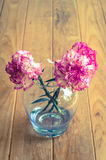 Pink carnations flower in a grass vase Royalty Free Stock Images