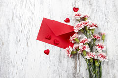 Pink carnations, hearts and red envelope Stock Photography