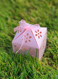 Pink carved gift box on green grass. Hand made gift box with ribbon bow on the green background Royalty Free Stock Image