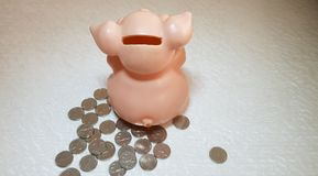 Piggy bank rear view with big ears and a tail standing on group of one Israeli sheckel coins. Pink ceramic piggy bank rear view with big ears and a tail standing stock photo