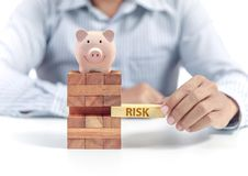 Pink ceramic piggy bank with wooden stack toy, risk concept stock photo