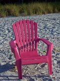 Pink chair on a beach. A pink Adirondack chair on a sandy beach in the sun Royalty Free Stock Photos