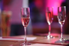 Pink champagne glass. The table in the restaurant. A glass of pink champagne close-up royalty free stock photos