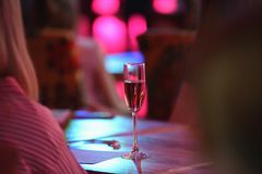 Pink champagne glass. The table in the restaurant. A glass of pink champagne close-up stock images