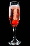 Pink champagne with maraschino cherry. Elegant flute of effervescent pink champagne with bubbles flowing from a maraschino cherry for a romantic date over a stock image