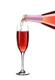 Pink champagne pouring in a glass. Stock Photos