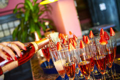 Pink champagne. Pouring pink champagne on a tray with strawberries Stock Photos