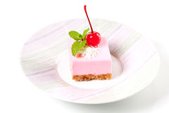 Pink cheesecake with maraschino cherry and mint Stock Photos