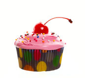 Pink Cherry Cupcake. Delectable pink cupcake topped with a cherry and multi-colored sprinkles.  Shot on white background Royalty Free Stock Photos