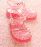 Pink children's footwear on pink towel Stock Image