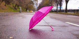 Pink children's umbrella on the wet asphalt Stock Image