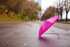 Pink children's umbrella on the wet asphalt Royalty Free Stock Photo