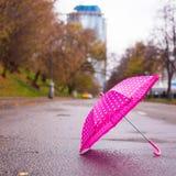 Pink children's umbrella on the wet asphalt Royalty Free Stock Images