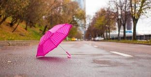 Pink children's umbrella on the wet asphalt Stock Images