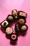 Pink chocolate. Handmade chocolates on pink background royalty free stock photos