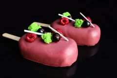 Pink chocolate glazed gelato ice cream popsicles with berries royalty free stock photos