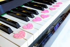Pink chocolate on key piano. Pink-heart chocolate on key piano stock photo