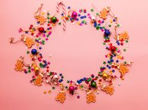 Free Pink Christmas Background With Frame Made Of Multicolor Christmas Balls, Gingerbread People And Bright Star Confetti. Chistmas And Stock Photo - 134533770
