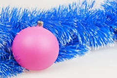 Pink Christmas ball with blue garland Royalty Free Stock Image
