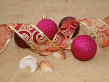 Pink christmas balls in sand Stock Photos