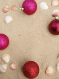 Pink christmas balls in sand Stock Photo