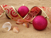 Pink christmas balls in sand Royalty Free Stock Image