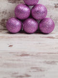 Pink christmas balls in a stack over wooden background Stock Image