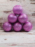 Pink christmas balls in a stack over wooden background Royalty Free Stock Photography