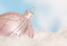 Pink christmas bauble in snow Royalty Free Stock Images