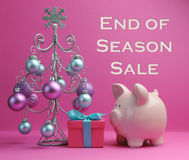Pink Christmas End of Season Sale. End of Season Sale savings with pink piggy bank and Christmas Tree with baubles and prsent gift box against a pink background Stock Image
