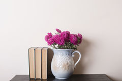 Pink chrysanthemum in a clay rarity vase and books on a wooden table. Light background Stock Photography
