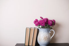 Pink chrysanthemum in a clay rarity vase and books on a wooden table. Light background Stock Image