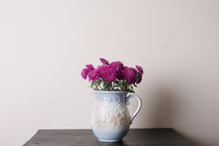 Pink chrysanthemum in a clay rarity vase o. N a wooden table, light background Royalty Free Stock Photo