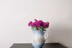 Pink chrysanthemum in a clay rarity vase. On a wooden table, light background Royalty Free Stock Images