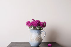 Pink chrysanthemum in a clay rarity vase. On a wooden table, light background Royalty Free Stock Photos