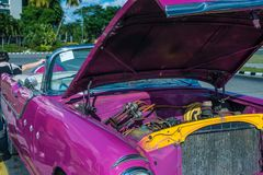 A pink classic car in Cuba. HAVANA, CUBA pink classic American car in Havana with the hood popped, showing off the motor Royalty Free Stock Images