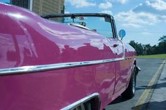 A pink classic car in Cuba. HAVANA, CUBA pink classic American car in Havana with the hood popped, showing off the motor Royalty Free Stock Photo