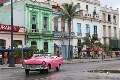 Pink classic car in front of old colonial buildings. Havana, Cuba - March 12, 2018: a pink classic car passes in front of old spanish buildings Stock Photography