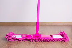 Pink cleaning mop on wooden floor Stock Photo