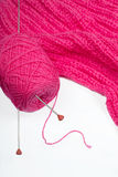 Pink clew with 2 needles is on Pink knitted linen Stock Photo