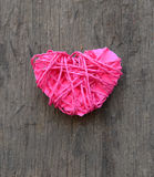 Pink clew in shape of heart on wooden background. Royalty Free Stock Image