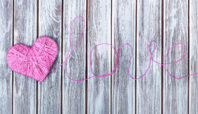 Pink clew in shape of heart and word love Stock Images