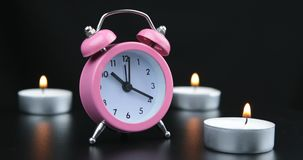 Pink clock with black numbers and arrows on black background. Pink clock with black numbers and arrows on black background stock footage