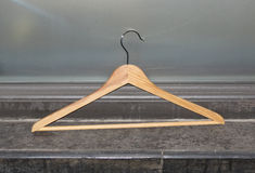 A pink clotheshanger. A wooden clothes hanger against a wall Stock Photos