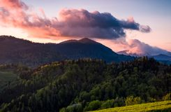 Pink cloud over the peak of a forested mountain Stock Photo