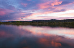 Pink Clouds over a Colorado lake at sunset. Sunset over a Colorado Lake with the mountains in the background royalty free stock photos