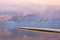 Pink Clouds over a fishing dock. Peaceful Colorado Lake with beautiful clouds reflecting in the lake stock photography
